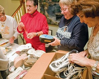 PACKING SHOES:  From left to right, Ginny Pugh, Mary Grace Bucko, Sally Perunko and Sally Pallante grab shoes and tape them together to be packed. Perunko and six others will travel to a village in El Salvador for mission work and will give the 134 pairs of gently worn shoes to the villagers.