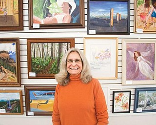 ART ON DISPLAY: Suzanne Bort Gray is the art coordinator at the Davis Family YMCA in Boardman. The pieces on display behind her were created by members of the Y and students in Gray's Y classes.