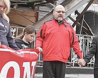 CLOSING PRAYER: Pastor Edward P. Noga, a member of ACTION, gives the closing prayer at an event in front of the former Linton Funeral Home on Youngstown's North Side. The city will demolish the structure shortly. Holding hands with the priest are, from left, Caitlyn Cominsky, 15, and her sister, Haylee, 11, both of Youngstown.