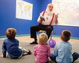 "STORY TIME: Bill Dick, of Goshen Township, reads from his new book, ""Santa Meets God's Ukrainian Children,"" to Zachary Smith, 4, of Columbiana, and Anna and Luke Shevchik, 2 and 5 respectively of Greensburgh, Pa. They were at the Children's Center for Science & wTechnology, 139 E. Boardman St., on Friday."