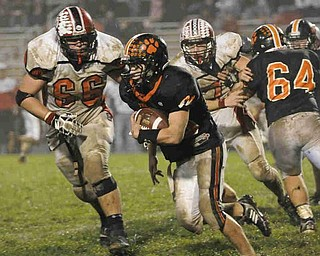 Springfield's (49) JIm Zubick runs the ball  against Columbiana's (66) Matt Douglas during their game on Friday night. Photo/Mark Stahl