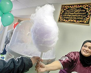 HANDY CANDY:  Manal Hamdan, of Boardman, gives a stick of cotton candy to a hungry onlooker. Hamdan and others celebrated their heritage during and open house for the Islamic Society of Youngstown on Sunday afternoon.