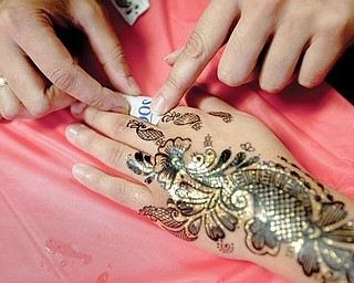 HANDIWORK:  A member of the Islamic Society of Youngstown carefully applies a temporary henna tattoo to a patron's hand. The Islamic Soctiety had an open house Sunday afternoon at its Homewood Avenue mosque.