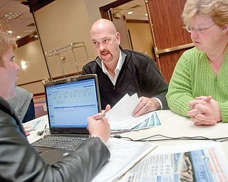 CRUISE CONTROL:  Chris Craft and Nina Combs, both of Boardman, finalize details on a cruise to Cancun, Mexico, with Apple Vacations. The two attended the first Travel Show at the Holiday Inn in Boardman on Sunday.