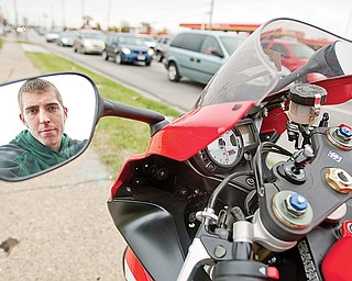 DANGER ZONE: Joey Dixon of Austintown stands alongside his brother's Suzuki motorcycle at one of the most-dangerous intersections in Mahoning County — Mahoning Avenue and state Route 46 in Austintown. Dixon's own motorcycle was totaled when he was in an accident at the intersection this past summer. He escaped without serious injury.