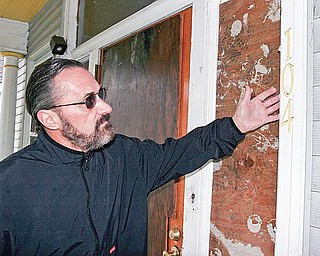 Dr. Robert Waddington, a member of the Lawrence County Historical Society, examines a house at 104 Wallace Ave, New Castle. He is one of a group New Castle area residents opposed to the house being demolished to make a parking lot. wd lewis
