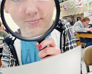 """LOOKING CLOSER: Alexis Cloud, an eighth-grader at Girard Junior High School, gets a closer look at fingerprints during a class project to find out who may have stolen some money from a teacher by using crime-solving techniques seen on popular TV shows such as """"CSI."""""""