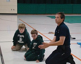 """FIRE SAFETY: Members of the Hubbard Volunteer Fire Department spent the afternoon recently with students at St. Patrick School for Fire Safety Month, which is October. Below, fourth-grader Daniel Robinson tries on the gear that firefighters wear going into a fire. Above, Daniel and schoolmate Vito DiTomasso listen intently as volunteer fireman Jim Petro gives fire safety tips. Students learned to """"Stop, Drop and Roll"""" if their clothing were to catch fire and were taught the importance of having working smoke detectors in their homes. After the indoor lessons, students went outside to see a firetruck and the equipment firefighters use, including the Jaws of Life."""
