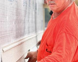 The Vindicator/Lisa-Ann Ishihara--- Jim Metzinger of Austintown hangs siding onto the new Kaluza house. Friday October 23, 2009