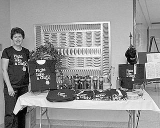 """Special to The Vindicator INSPIRING SLOGAN: T-shirts, designed in support of those with breast cancer and emblazoned with the slogan """"Fight Like a Girl,"""" are displayed by Pam Simpson at The Simpson Gallery, 2208 Elm Road, Warren. The clothing line and accessories, such as tote bags and water bottle, are being sold to raise funds for the Ireland Cancer Center at Trumbull Memorial Hospital to provide assistance for patients with cancer. The fundraiser will include the sale of tickets to win an """"All Pink Basket"""" containing a variety of clothing, candles, jewelry and accessories. For more information on the merchandise or store hours, call the gallery at (330) 372-1899."""