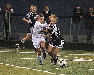 BALL BATTLE:  Fitch's Christian Goleno, left, battles Canfield's Gia Nigro for the ball during Monday's Division I district semifinal girls soccer game in Austintown. The Cardinals won 1-0 in overtime.