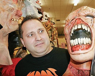 SCARY JOB: Jeff Lyda, co-owner of Halloween Mania in Austintown, checks out masks at the store. He said a lack of stress is making Halloween a popular adult event.