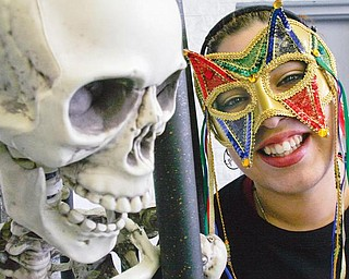 WHO'S THAT?: Milly Lopez, an employee at Halloween Mania, tries on a mask at the store. Sales have been strong this month at the seasonal Halloween shop.