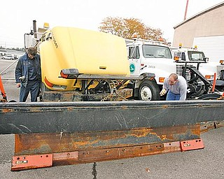 ODOT workers Matt Kotanchek and John Keeney check over one of the plow/slag trucks at the ODOT garage in Canfield.