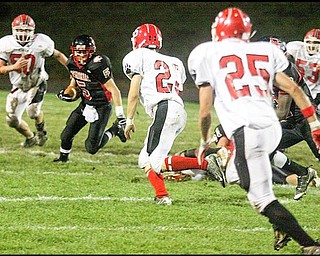 FOOTBALL - Skevo Zambellis of Campbell is being pursued by (50) John DeSantis (20) Mike Kunzer and (25) Dylan Duchek of Struthers during their game Friday night. - Special to The Vindicator/Nick Mays