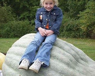 Kaitlin Burich of Austintown sits atop a giant gourd!