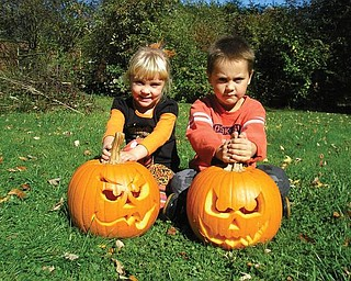 Jacob, 6, and Noelle, 3, show off the pumpkins they carved at their annual pumpkin-carving party in Boardman.