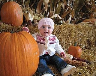 A LITTLE PUNKIN: Stella Schiavone, granddaughter of Dan Schiavone of Boardman, is barely a match for this huge pumpkin!