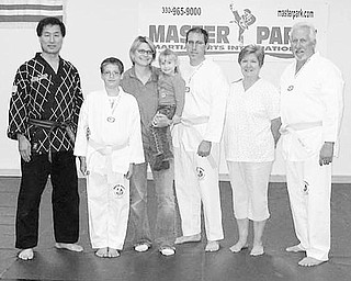 Special to The Vindicator UNITY: Three generations are represented in a martial-arts training class conducted at Master Park Martial Arts International. Among those participating in or supporting the program are, from left, Master Park; Branden St. Clair, 13, who was the first in his family to get involved in martial arts; his mother, Patricia, holding his sister, Tori; his father, Brian; and his grandmother, Wendy, and grandfather, Robert St. Clair. The family has found martial-arts training promotes good health and fun while helping participants develop confidence, a positive attitude, discipline, respect and courtesy. For more information, call (330) 965-9000 or e-mail masterpark@masterpark.com.