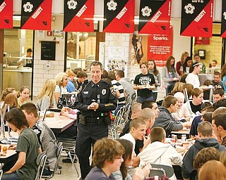 GETTING REACQUAINTED: Canfield Patrolman Paul Lasky walks through the cafeteria of Canfield High School and converses with students. Lasky returned to his place as the school resource officer for Canfield Local Schools on Monday after a two-month absence.
