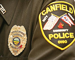 SERVE AND PROTECT: Paul Lasky, juvenile officer with the Canfield Police Department, displays this badge at Canfield High School. Lasky has more than 30 years of experience in law enforcement and has been involved with Canfield schools since 2000.