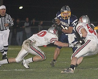 MCDONALD - (31) Zach Tura picks up yardage against (10) Miles Chapman and (36) Jaren Wickham of the Chieftains defense Saturday night. - Special to The Vindicator/Nick Mays