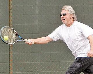 TENNIS ANYONE? Mike Phelps of Boardman enjoys a game of tennis at Boardman Park, enjoying the unseasonably warm weather Monday.