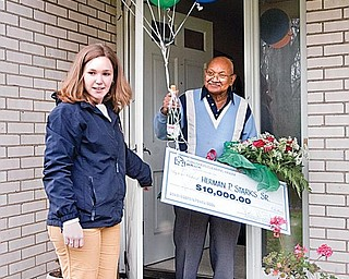 LUCKY WINNER: The Publishers Clearing House's Kaitlyn McCoy, of Long Island, presents a check for $10,000 to Herman Starks at his home in Liberty on Tuesday afternoon.