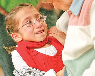 OVERWHELMED: Suzie Mazzocco, 9, gives her grandmother, Irene Consiglio, a hug after the child was surprised with tickets to a Miley Cyrus concert. The tickets and other gifts were presented at an assembly at Struthers Elementary School on Wednesday. Suzie has a rare bone-growth disorder that results in dwarfism. She has had 17 surgeries.
