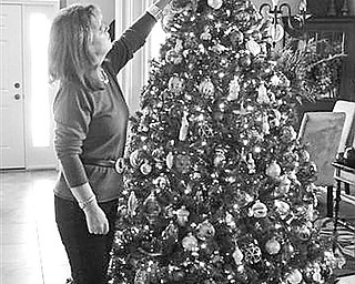 Special to The Vindicator FINAL TOUCH: An ornament is placed near the top of one of the many Christmas trees in her home by Pat Tingle as she prepares to welcome guests during home tour sponsored by Columbiana Women's Club and a brunch at the club, 121 N. Main St.