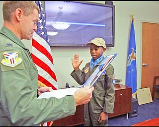 The Vindicator/Robert K. Yosay -----  -  Alan Hinton 11 of Youngstown  gets sworn in as a second lieutenant by  Colonel Craig Peters a- Alan was pilot for a day at the Youngstown Airbase - 11182009