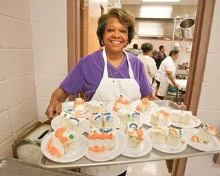 SWEET TREAT: Rosalind Willis, coordinator of the Wednesday free lunch at St. Andrewes AME Church, holds a tray of pieces of cake. The church recently revived its tradition of offering a free meal. Those attending are served restaurant style. This week, about 153 people attended.