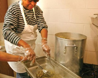COOK IN THE KITCHEN: Ethel White, a member of St. Andrewes African Methodist Episcopal Church, 531 W. Earle Ave., Youngstown, transfers steaming green beans to a serving dish from a large kettle. She's among church members who volunteer at the free lunch for all on Wednesdays.