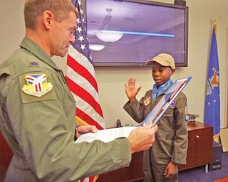 """TAKING THE OATH: Alan Hinton, of Youngstown's North Side, who was chosen for the """"Pilot for a Day"""" program at the Youngstown Air Reserve Station, is sworn in Wednesday by Lt. Col. Craig Peters, the operations group commander."""