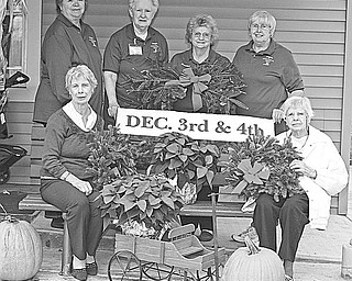 """Special to The Vindicator/ Nick Mays COLORFUL EVENT: Displaying colorful poinsettias and other items, which will be available during the """"Christmas Celebration for Children"""" to be sponsored by the Friends of Children's Aid Society of Mercer County, are, from left seated, Darlene McBride and Helen Louise Donner, and standing, Barb Lambert, Joan Foster, Carol Smith and Liz Bolster."""