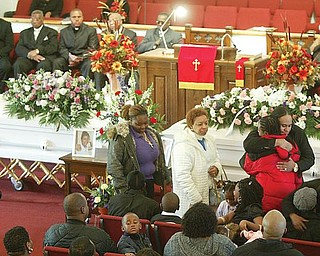Mourners embrace family members of Wilneice Green, and her daughter, Ja'Brayasia (also written as Ja-Brajasia), during a funeral service Monday at Elizabeth Missionary Baptist Church in Youngstown. About 300 attended the service. The Greens were murdered Nov. 15 in their home in Liberty Township.
