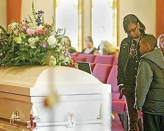 QUIET MOMENT: Rasheedah Hudson of Youngstown and her son, Charles, 4, pause for quiet reflection at the coffins of Wilneice Green and her daughter, Ja'Brayasia, during the funeral service Monday. Pastor Sylvia Jennings of Oak Baptist Church, Youngstown, where the Greens attended, offered the eulogy.