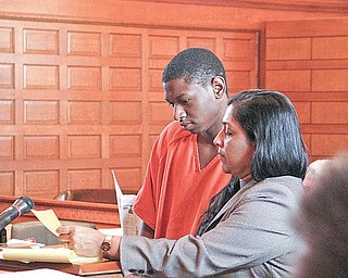 IN COURT: Oryan Miller of Warren reads along with his attorney, Sarah Kovoor, in Trumbull County Common Pleas Court.