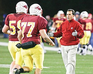 Cardinal Mooney head football coach PJ Fecko talks to players returning to the sideline.