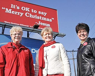 SENDING A MESSAGE: The Merry Christmas Billboard Ladies, from left, Joanne Brown of Poland, Pat See of Canfield and Linda Bennett of Niles, stand in front of one of their billboards at U.S. Route 422 and Robbins Avenue, Niles. Also in the group is Judi Hanna of Boardman. The billboard movement is catching on in other states.