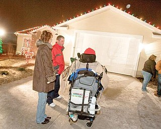 Snow flakes fall as Joe Kaluza talks with his sister, Anna Fitzgerald, and Ed Wojciechowski, of Edison Lighting during a Christmas lighting ceremony at the newly constructed home on Monday evening. Edison Lighting of Boardman was responsible for installing the Christmas lights.