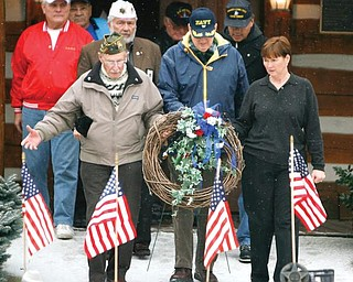 PRESENTING THE WREATH: A wreath was placed at the base of the Mahoning County Veterans Monument for veterans of all wars during a service at the Canfield Fairgrounds to commemorate the bombing of Pearl Harbor on Dec.  7, 1941. Carrying the wreath Monday are, from left, Raymond Braidich, Milton Kochert and Jan Brown.