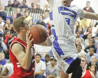 CLIPPERS CLIPPED: Youngstown Christian's Caleb Yanno (3) blocks a shot by Columbiana's Zach Chaplow (32) during Tuesday's game at Youngstown Christian High School. The Eagles defeated the Clippers, 93-71.