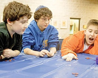 DREIDEL GAME: From left, Adam Redlich, 11, of Youngstown, Ben Feuer, 12, of Canfield and Jared Rosenberg, 11, of Youngstown wait for a dreidel to stop spinning while playing a game for beans during a Hanukkah event at Temple El Emeth in Liberty on Wednesday. Hanukkah begins at sundown today and lasts for eight days.