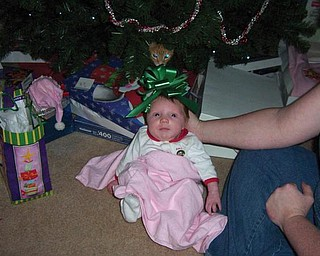 Little Abigail Shay was only 1 month old in this 2008 picture of her under the tree on her first Christmas. Just above her in the tree is Badger the cat.