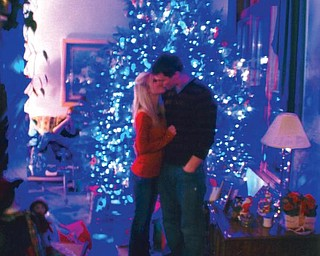 Billy Speece of Canfield and his girlfriend, Ashley Gresh of Canfield, share a kiss in front of the family's Christmas tree, which they found at the Speece Tree Farm in Canfield.