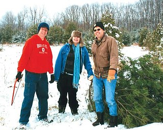 Billy Speece , Karissa and Tom drag a tree from Speece Tree Farm.