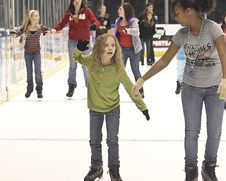 The Vindicator/Lisa-Ann Ishihara ---L-R Olivia Vaupel of Fowler Township and her friend Jahnai Bridges (12) of Orlando, FL- ice skate at the Covelli Centre for First Night Youngstown 2010