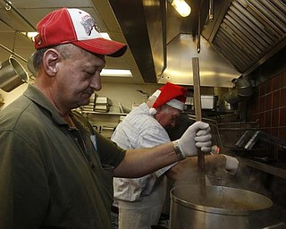 The Vindicator/Lisa-Ann Ishihara -- Rick Bowser of Andover volunteers his time in the kitchen at Aulizio's Banquet Center in Warren for the free christmas dinner