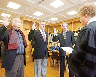 TAKING AN OATH: Judge Mark A. Belinky of Mahoning County Probate Court, foreground, swears in the new commissioners to the Mill Creek MetroParks Board. They are, from left, Daniel De Salvo of Boardman, John Ragan of Canfield and Dr. Robert Durick of Struthers. They were sworn in Wednesday.